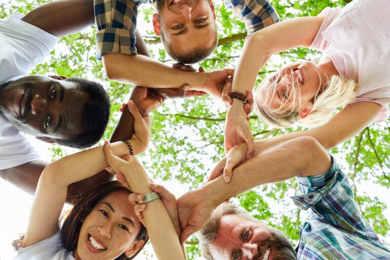 Junge Leute verschränken die Hände zum Zeichen der Solidarität und Gemeinschaft